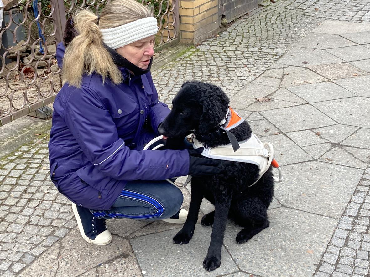 Frau Larsen kniet neben dem sitzenden scharzen Blindenführhund Chepi, und streichelt ihn. Frau Larsen, Vorstandsmitglied des ABSV, hat sich sehr für ein assistenzhundfreundliches Berlin Charlottenburg/Wilmersdorf eingeetzt.