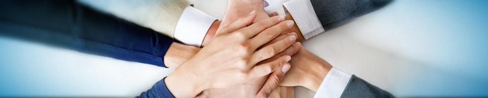 Acht Hände treffen sich in der Mitte und liegen übereinander