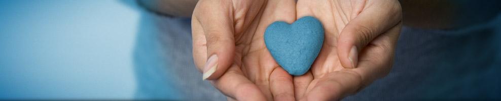 Zwei Hände halten ein blaues Herz