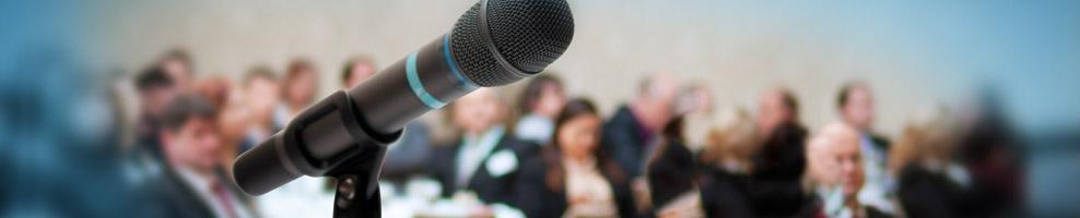 Nahaufnahme Mikrofon, im Hintergrund Zuschauer