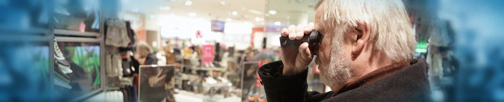 Sehbehinderter Mann mit Monokular im Kaufhaus