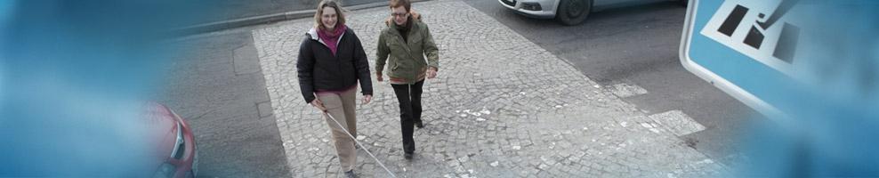 Frau mit Blindenstock, überquert die Straße auf einem Zebrastreifen
